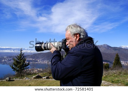 Nature photographer with digital camera on top of the mountain, Epirus, norhern Greece. (near Vikos canyon) - stock photo