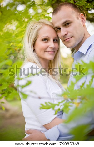 Nature portrait of attractive young couple cuddling. - stock photo