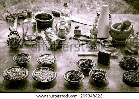 Nature's Pharmacy.  Vintage mortar and pestle surrounded by various herbs, ingredients and tonics. - stock photo