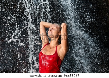 Nature spa concept - Young and emotional girl in red tank-top enjoying jungle waterfall - stock photo