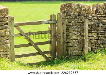 Nature summer landscape. Countryside view and rustic gate in drystone wall in village Bibury England, UK. - stock photo