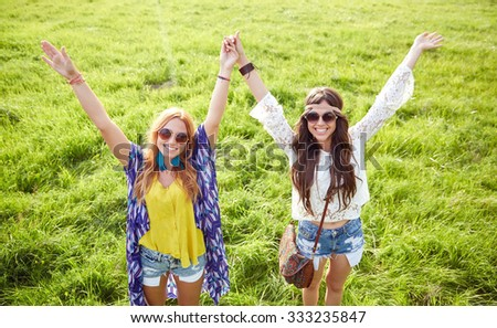 nature, summer, youth culture, friendship and people concept - smiling young hippie women dancing on green field - stock photo