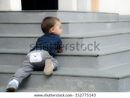 Naughty baby lying on the stairs outdoor - stock photo
