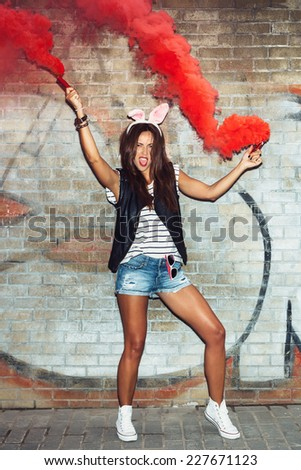 Naughty hipster girl in pink rabbit ears with red smoke bombs. Outdoors lifestyle portrait - stock photo