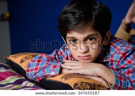 Naughty little boy. Angry little boy frowned while laying on bed and looking at camera - stock photo