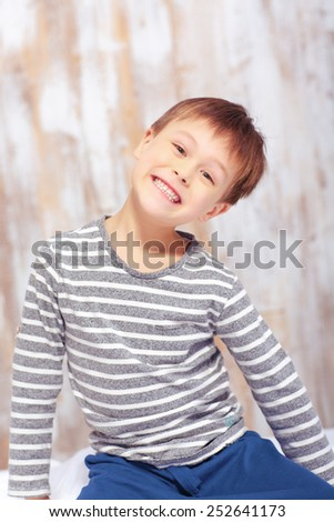 Naughty little boy. Sad little boy keeping arms crossed while sitting in bed in pajama and looking at camera - stock photo