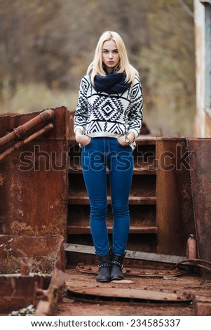 Naughty young cute lady in sweater and scarf outdoors full length portrait in abandoned place - stock photo