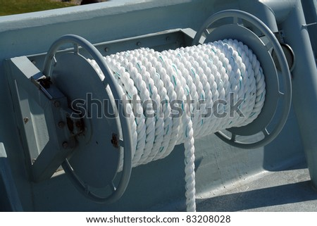 Nautical boat rope rolled on a metal drum winch on deck - stock photo