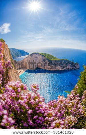 Navagio beach with shipwreck and flowers against sunset, Zakynthos island, Greece - stock photo