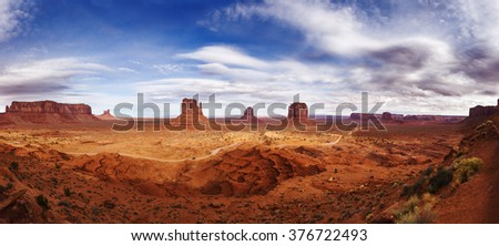 Navajo Reservation in Arizona, USA. Panoramic View on the beautiful red-orange rocks in light of the white-purple sunset in Monument Valley. - stock photo