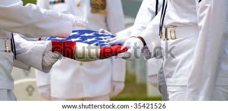 Naval Honor Guard folding US Flag over casket during funeral at Arlington National Cemetery - stock photo