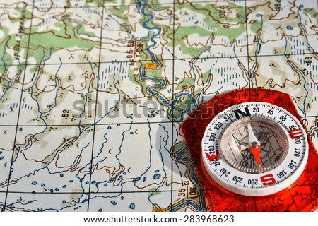 Navigation equipment for orienteering. Magnetic compass and topographic map. - stock photo