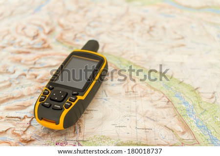 Navigation outdoors: hand held GPS on a hiking map. - stock photo