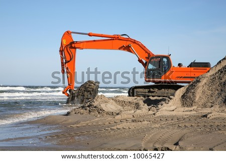 Navvy digging sand for coast protection project - stock photo