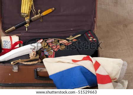 Navy officer's coat with military medals in an old suitcase - stock photo