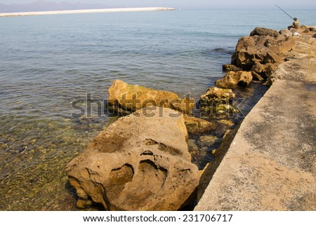 Navy Pier, ukreplennyay boulders, and fisherman with a fishing rod on a background of the sea horizon - stock photo