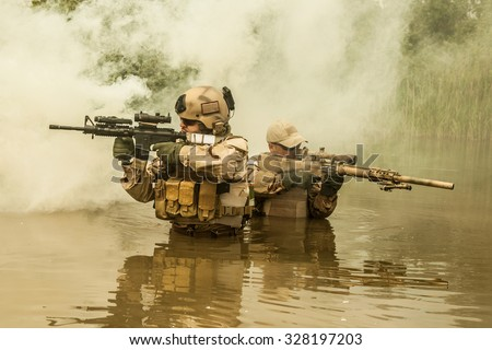 Navy SEALs crossing the river with weapons  - stock photo