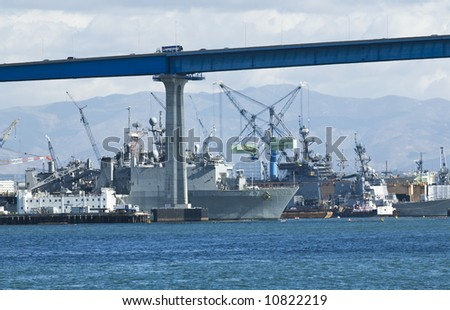 Navy Ship Yards in San Diego California as viewed from Coronado Island. The Coronado Island Bridge is visible in the top of the frame. - stock photo