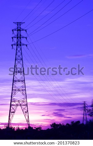 Near and Far High-Voltage Tower Connected by Wires at Sunset - stock photo