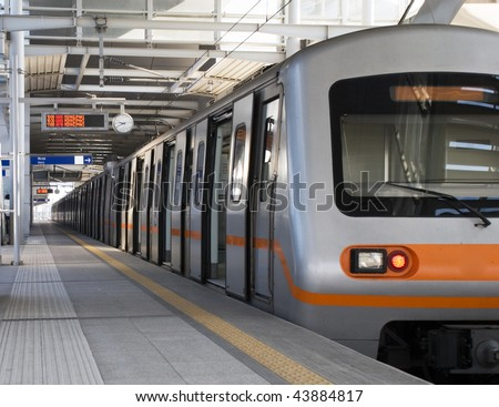 Nearly empty urban metro station with departing train - stock photo