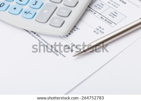 Neat calculator with silver pen and utility bill under it - stock photo
