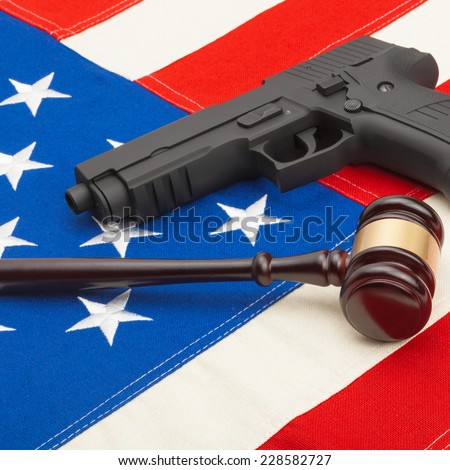 Neat judge gavel and gun over USA flag - studio shoot - stock photo