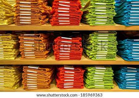 Neat stacks of folded clothing on the shop shelves - stock photo