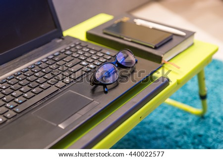 Neat tabletop workstation with eyeglasses lying on the keyboard of an open laptop computer with a diary and mobile phone alongside - stock photo