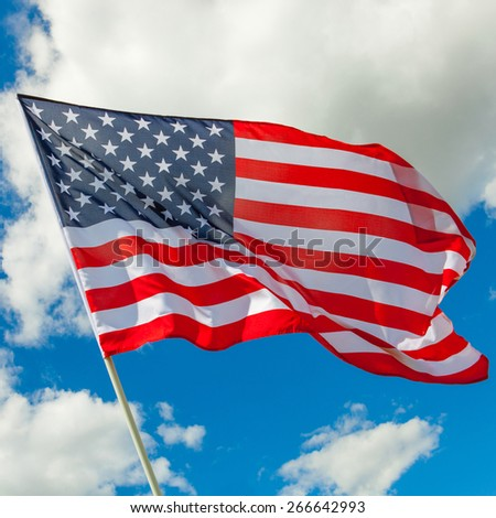 Neat US flag and cumulus clouds behind it - stock photo