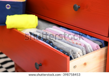 Neatly folded clothes in open drawer, close up - stock photo