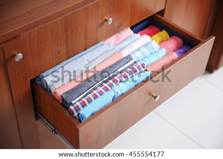 Neatly folded clothes in wooden drawer - stock photo