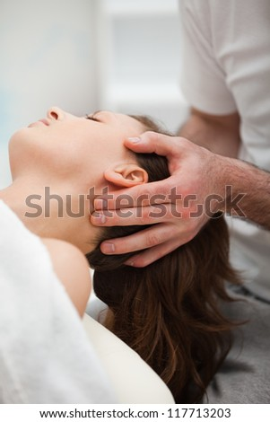 Neck of a woman being manipulating by a therapist in a room - stock photo