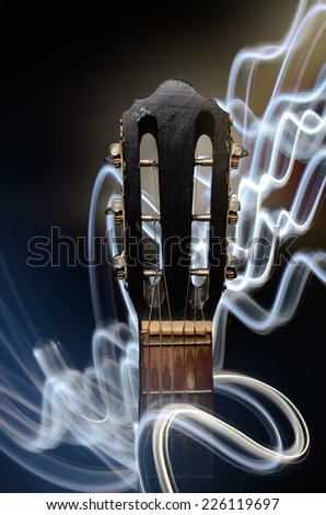 Neck of acoustic guitar with lighting waves on black background - stock photo