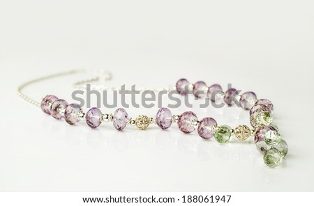 necklace made of transparent amethyst and prasiolite on gray background - stock photo