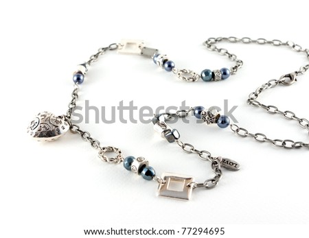 Necklace with blue pearls and a heart isolated on white background - stock photo