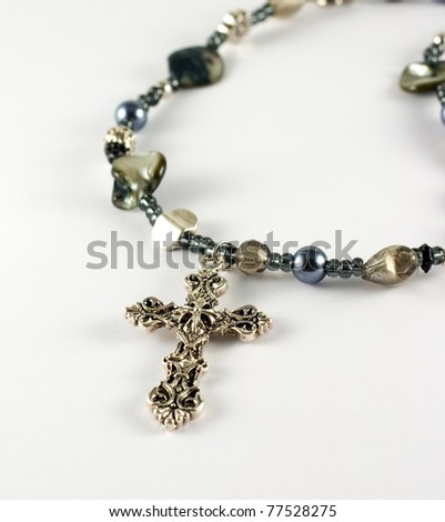 Necklace with crucifix on white background - stock photo