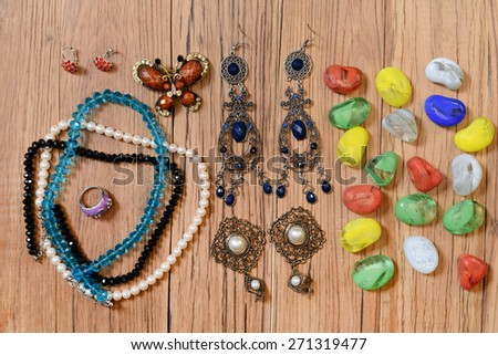 Necklaces, earrings and colored glass on the wooden table - stock photo