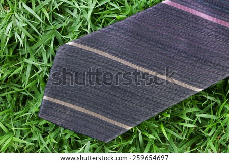 Necktie put on the green grass as a background represent the accessory of formal business uniform. - stock photo