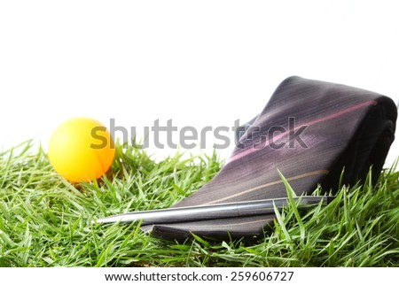Necktie with orange ball and chrome pen put on the green grass as a background represent the accessory of formal business uniform. - stock photo
