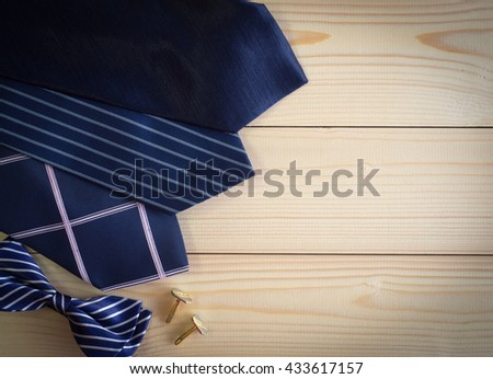 Neckties and bow and cufflinks on the wooden table with copy space - stock photo