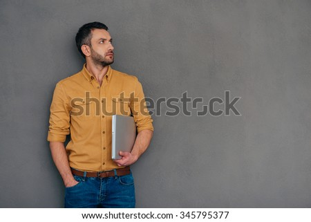 Need an expert advice? Thoughtful mature man carrying laptop and looking away while standing against grey background - stock photo