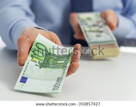 Need money? Businessman offering money to you - stock photo