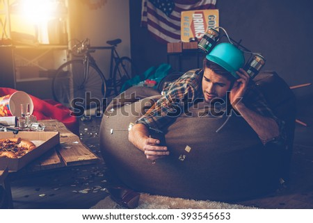 Need to delete that picture! Handsome young man in beer hat using his smart phone while lying on bean bag in messy room after party - stock photo
