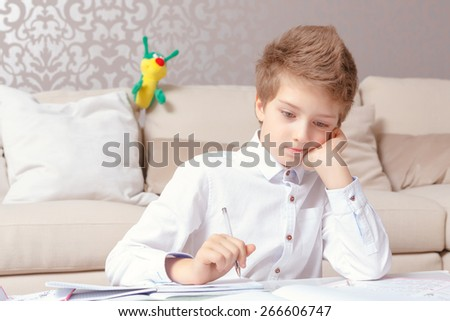 Need to think. Small schoolboy thoughtfully holds his chick with a hand sitting by the table and doing tasks  - stock photo