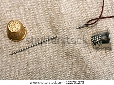 needle and thimble natural linen texture for the background - stock photo
