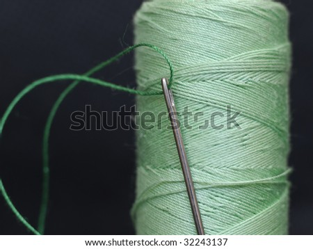 needle in green bobbin on black - stock photo