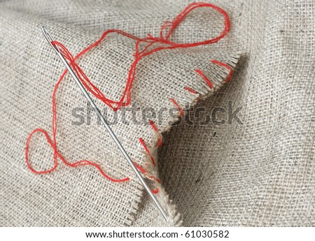 Needle with red thread that executes the stitches on sacking - stock photo