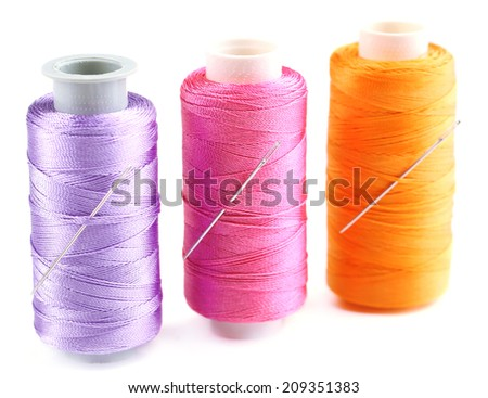 Needles and spools of thread isolated on white - stock photo