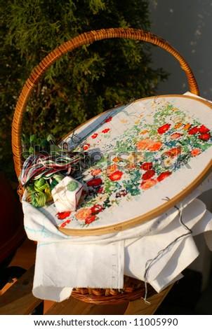 needlework of generic flowers on textile (cross stitch) - stock photo