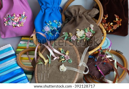 Needlework. Process embroidery with satin ribbons of gift bags for cosmetics - stock photo
